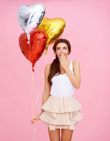 Cute beautiful sexy woman with three colourful red , gold and silver heart shaped party balloons holding her hand to her mouth in surprise at her Valentine gift photo