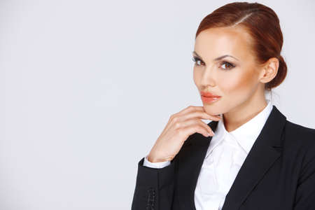 contemplative: Attractive pensive businesswoman in a black jacket looking at the camera with her hand to her chin, head and shoulders studio portrait with copyspace Stock Photo