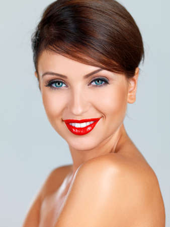 Head and shoulders portrait of a beautiful smiling fashion model wearing bright red lipstick photo