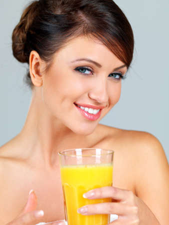 Smiling beautiful woman with bare shoulders drinking a large glass of freshly squeezed orange juice photo