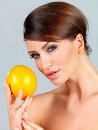 Sensual beautiful woman holding up a ripe fresh orange in her hand on a grey studio background photo