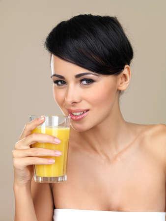 verre de jus d orange: Belle femme brune en dégustant un verre de saine jus d'orange fraîchement pressé isolé sur un fond de studio beige Banque d'images