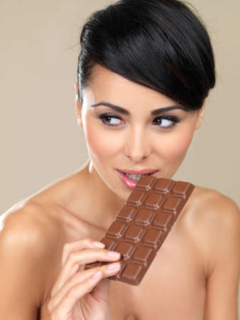 surreptitious: Beautiful woman with a bar of chocolate first checking to see that no one is watching her before taking the first bite isolated on beige