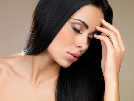 Beautiful sensual brunette woman with her eyes closed and her head tilted forwards with her hand to her forehead
