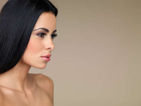 Side view head and shoulders portrait of a beautiful brunette woman daydreaming with a faraway expression in her eyes on a beige studio background with copyspace photo