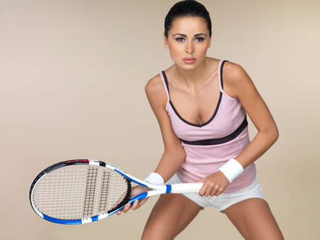 Attractive woman in sportswear playing tennis crouching in the ready position holding her racquet in front of her isolated on beige Stock Photo - 17480993