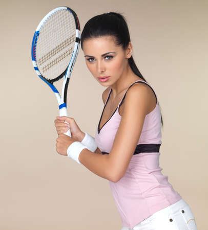 backhand: Attractive woman in sportswear playing tennis holding her racquet in both hands ready to play a backhand shot isolated on beige