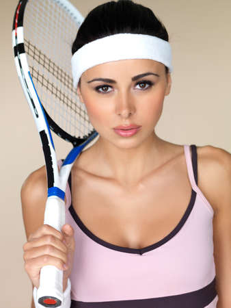 human sexual activity: Beautiful female tennis player wearing a headband holding her racquet over her shoulder