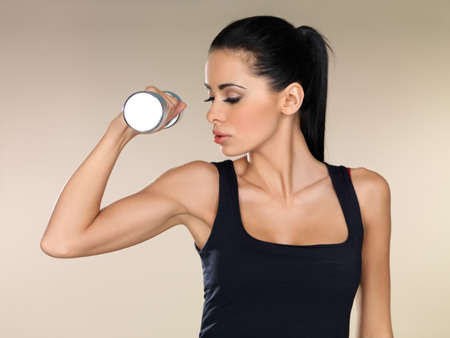 Beautiful brunette woman working out with a dumbbell raising and flexing her arm to strengthen her biceps photo