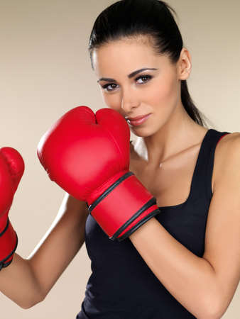 Attractive young female boxer wearing a pair of red boxing gloves with her fists raised close to her face in the defensive position photo
