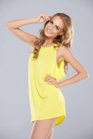 miniskirt: Joyful blonde woman with a beautiful smile posing in a trendy yellow miniskirt, three quarter studio portrait
