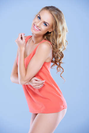 skimpy: Beautiful sexy blonde fashion model looking at the camera with a lovely vivacious smile while posing in a short apricot coloured top Stock Photo
