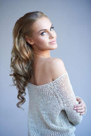 Mooie elegante vrouw met lang krullend blond haar dragen van een stijlvolle off the shoulder top kijkt terug over haar schouder met een glimlach Stockfoto