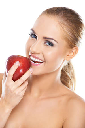 a tooth are beautiful: Laughing blonde woman with bare shoulders holding a large ripe red apple in her hand in a depiction of healthy eating