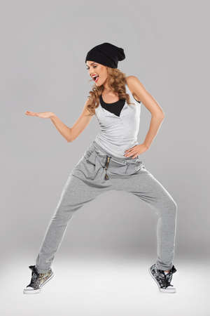 vivacious: Vivacious beautiful young woman in casual clothes and a black cap singing and striking a pose Stock Photo