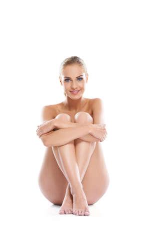 corps femme nue: Portrait artistique d'une belle femme qui pose nue implicite séance sur le sol avec ses jambes repliées devant elle, portrait en studio sur fond blanc