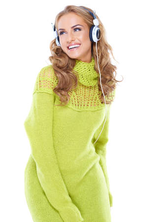 Happy woman with long curly blonde hair enjoying her music laughing over her shoulder as she sways to the rythm isolated on white photo