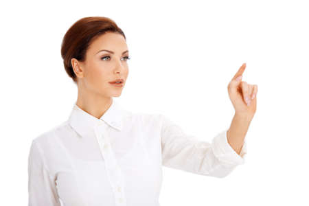 fingertip: Beautiful woman using a virtual screen pointing with her finger towards blank copyspace with her eyes focused on her fingertip