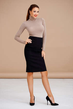 Fashionable brunette in turtleneck sweater and pencil skirt photo