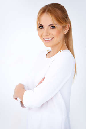 Portrait of happy attractive young blonde woman looking at camera with crossed arms Stock Photo - 17968802