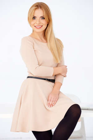 Blond girl in pretty short dress posing and smiling. White background Stock Photo - 17968803