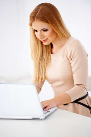 Portrait of a smiling sexy blonde woman working on a laptop at her desk Stock Photo - 17968836