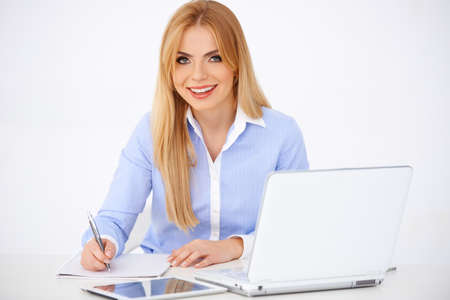 Blond girl with laptop and tablet, sitting at her desk writing with pen. White background Stock Photo - 17968805