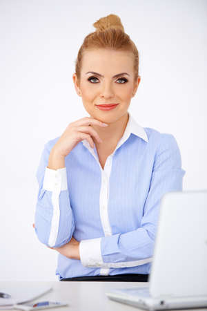 Blonde attractive young woman sitting at her desk with her laptop in front of her Stock Photo - 17968888