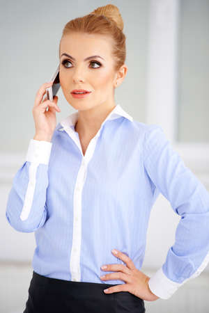 Pretty blond girl talking on her cellphone. White background Stock Photo - 17968878