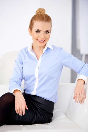 Pretty blond girl sitting on a sofa and smiling, while looking at camera photo