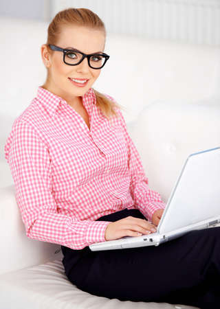 Pretty blond girl sitting on sofa with laptop and wearing black glasses. Stock Photo - 17968826