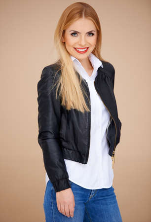 Stylish blond girl, wearing a leather jacket and jeans. Stock Photo - 17968923
