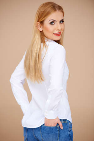 Beautiful blond girl wearing a white blouse and jeans. Back view Stock Photo - 17968890