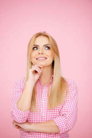 Thoughtful blond girl hatching an idea, on pink background photo