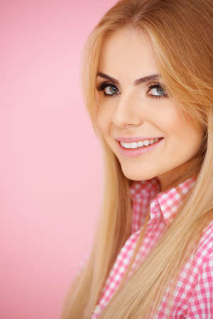 Smiling blond girl on pink background in checkered blouse, right side photo