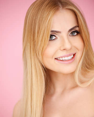 Beautiful smiling blond girl on pink background photo