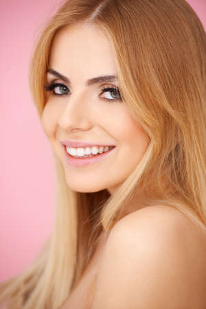 Portrait of a smiling blond girl on pink. Side view photo