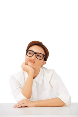 contemplates: Thoughtful businesswoman wearing glasses sitting at her desk pulling a face as she contemplates a difficult decision