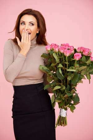 delighted: Beautiful brunette surprised with a bouquet of roses. On pink Stock Photo