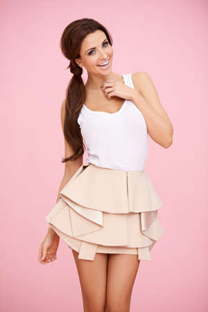 ponytail: Cute brunette in a short skirt posing before pink background