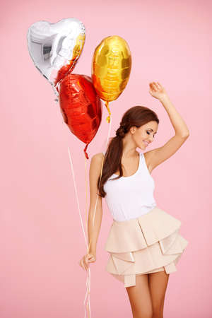 miniskirt: Cute dancing brunette with colorful heart shaped balloons on pink
