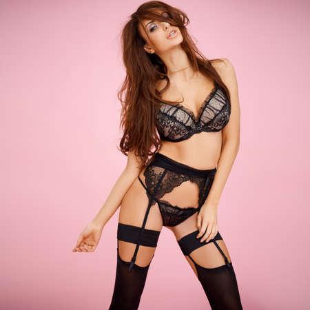 Belle brune en lingerie sexy en dentelle noire. Le rose