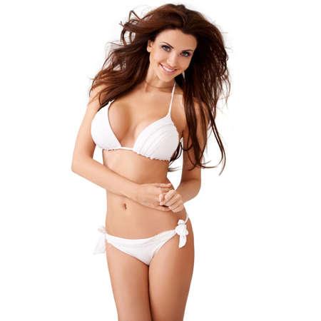 jungen unterw�sche: Vivacious sexy junge Br�nette Frau mit einem sch�nen L�cheln und ihr Haar weht im Wind posiert in einem wei�en Bikini drei Viertel isolierte Studio-Portr�t Lizenzfreie Bilder