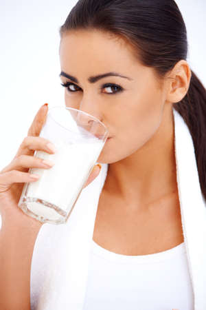 Cute healthy woman is drinking milk from a glass Stockfoto