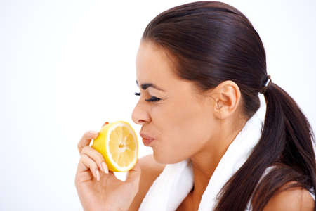 making a face: Young woman holding lemon while making a face Stock Photo
