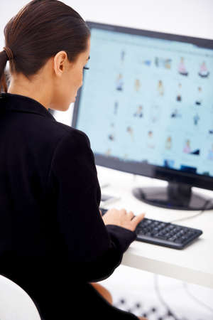 Young business woman sitting at her workplace and typing on computer keyboard photo