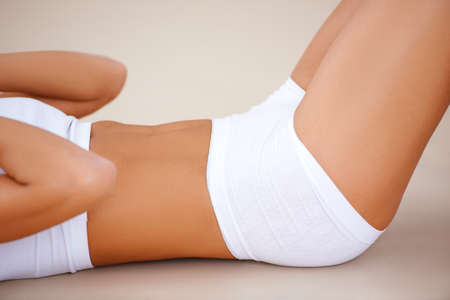 athletic body: Body part of fit woman  she doing exercises on the beige floor Stock Photo