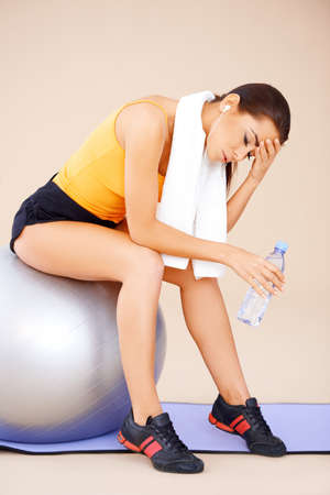 Young beautiful Woman sitting on fitness ball with towel around her neck photo