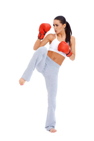 girl kick: Full body shot of female kick boxer over white background Stock Photo