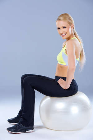 fit ball: Blond sporty woman sitting on fitness ball over gray background